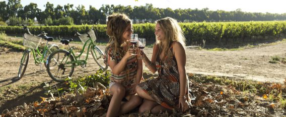 Dos mujeres jovenes disfrutando de un bici tour por las viñas de Chile