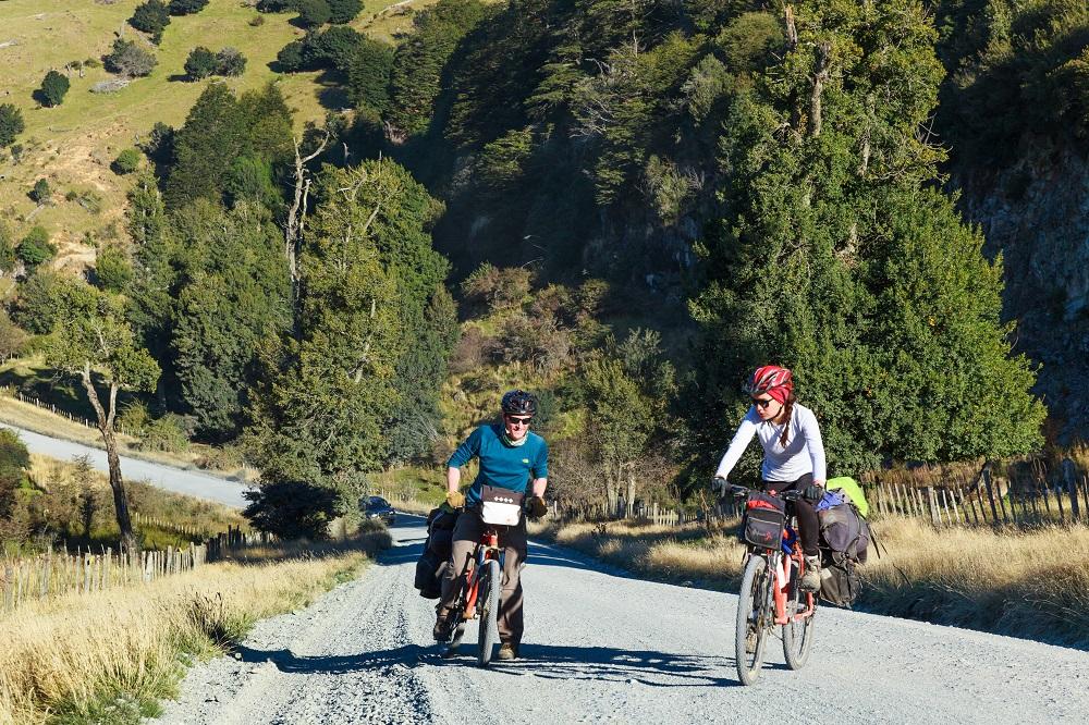 Personas disfrutando en bicicleta de los Verdes paisajes de la Carretera Austral