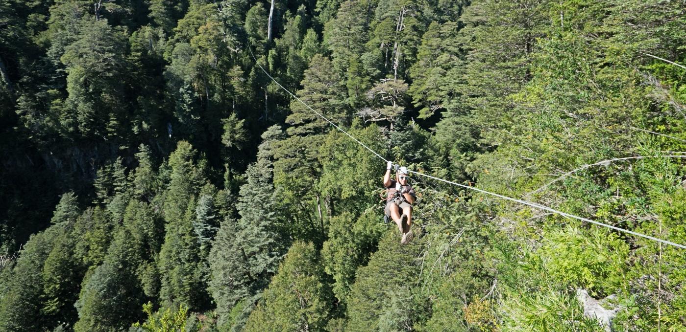 Imagen de un turista realizando canopy en puerto fuy