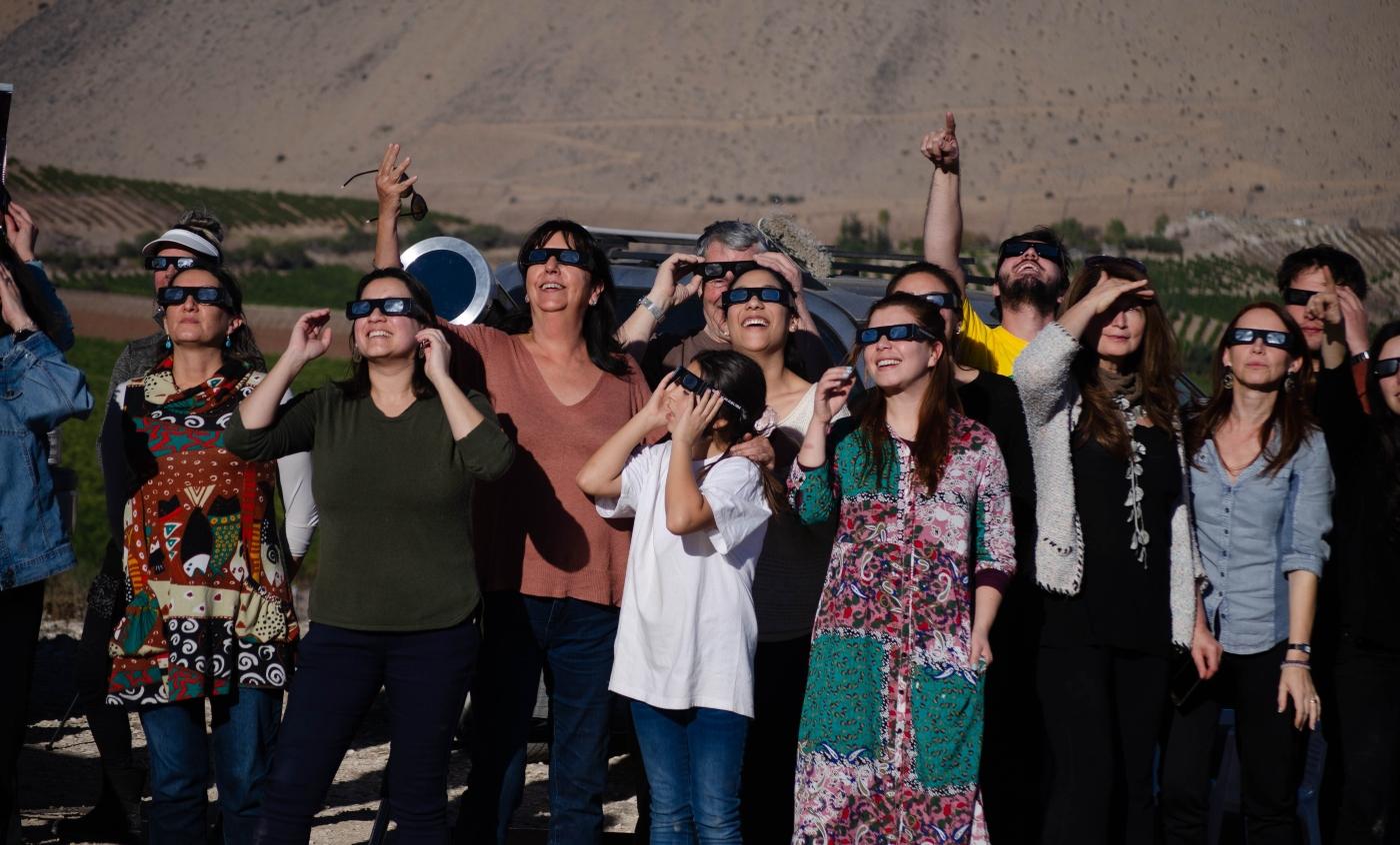 Imagen de un grupo de personas observando el eclipse solar en Chile con lentes de protección
