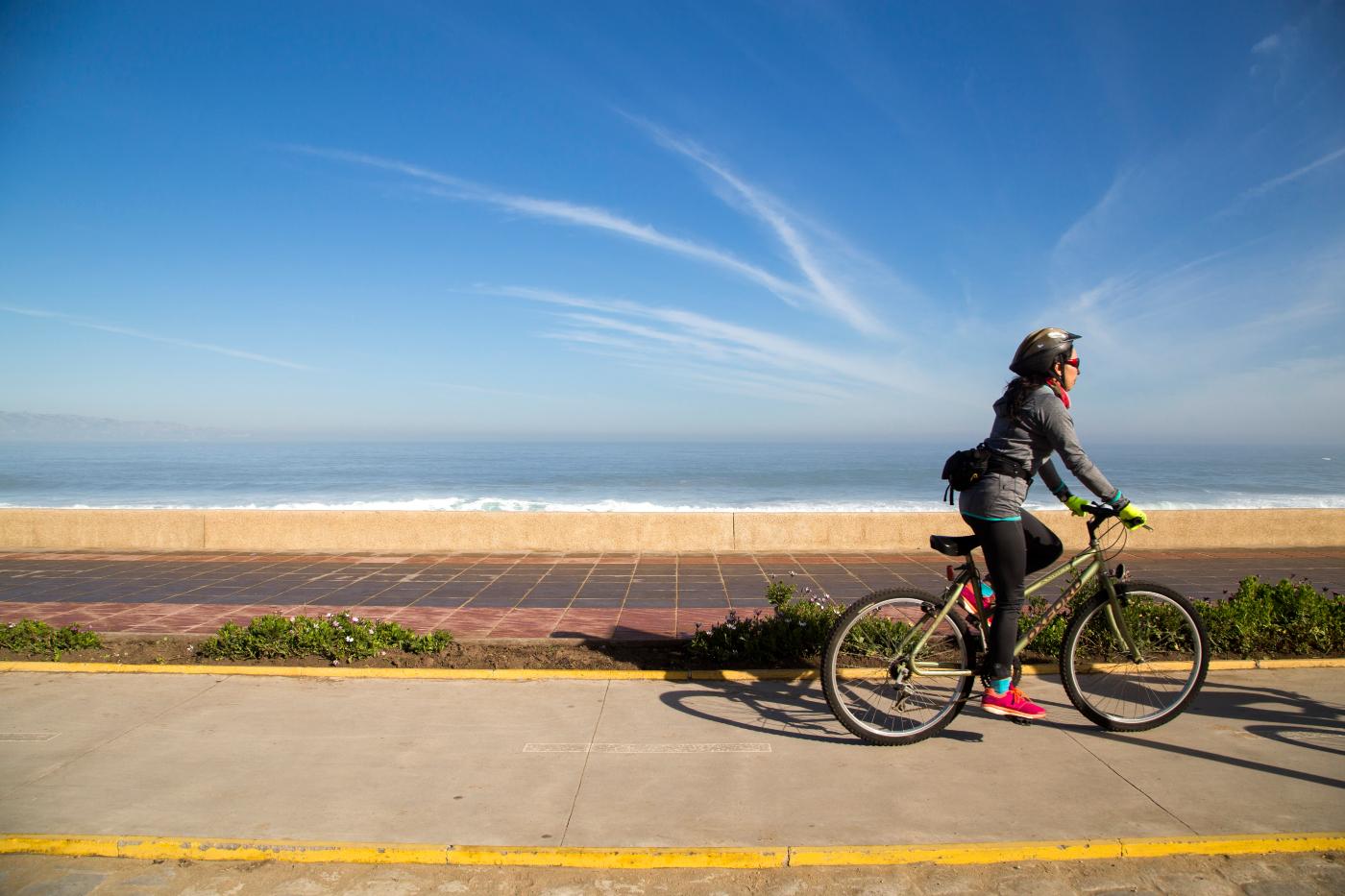 Imagen de una persona andando en bicicleta por la costa