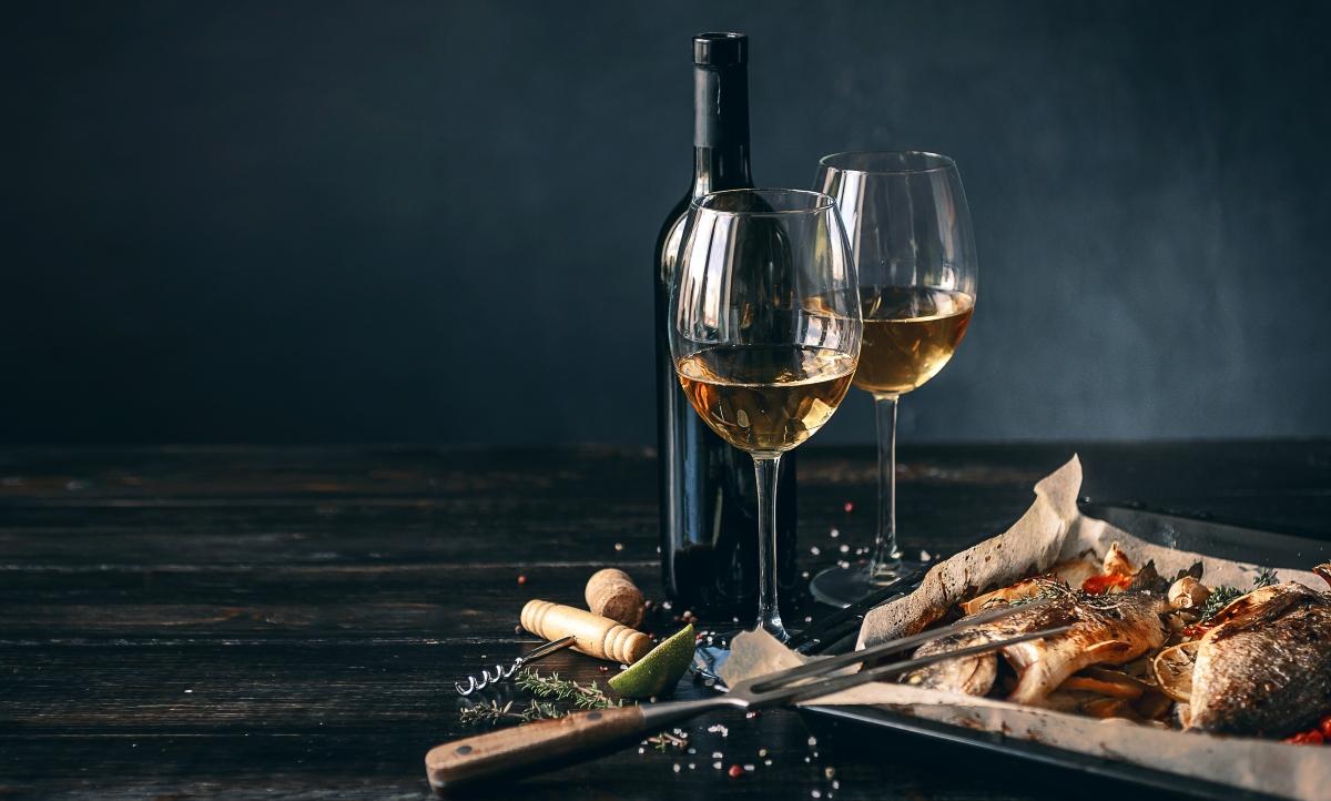 Imagen de una botella y copas de vino blanco