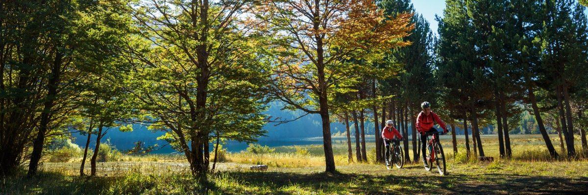 Imagen de dos turistas recorriendo Coyhaique en bicicleta
