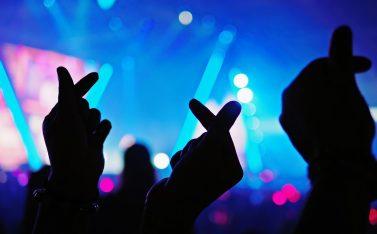 Imagen de manos de personas en un concierto con una señal de cariño coreana