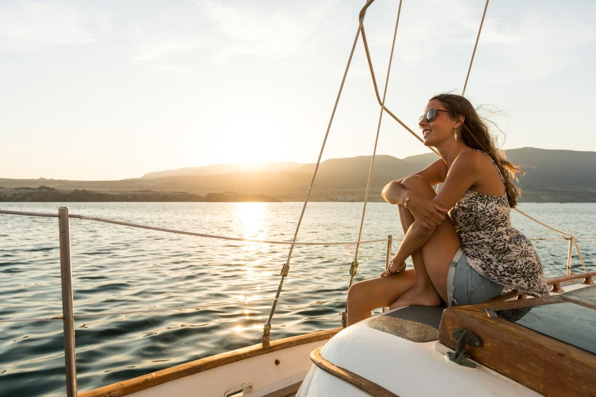 Mujer relajándose sobre un yate en medio del mar