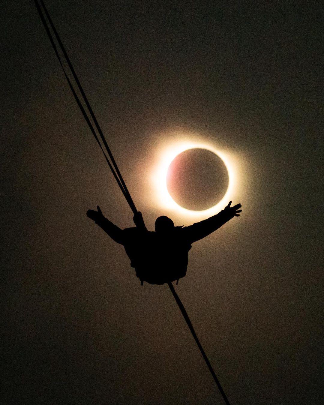 Imagen de un hombre caminando por una cuerda en medio del eclipse 2020