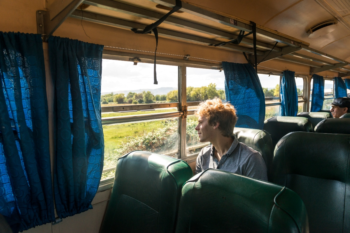 Imagen de una persona disfrutando del paisaje en el tren Ramal Talca Constitución