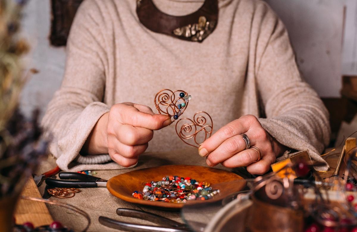 Imagen de una mujer mostrando su artesanía en cobre