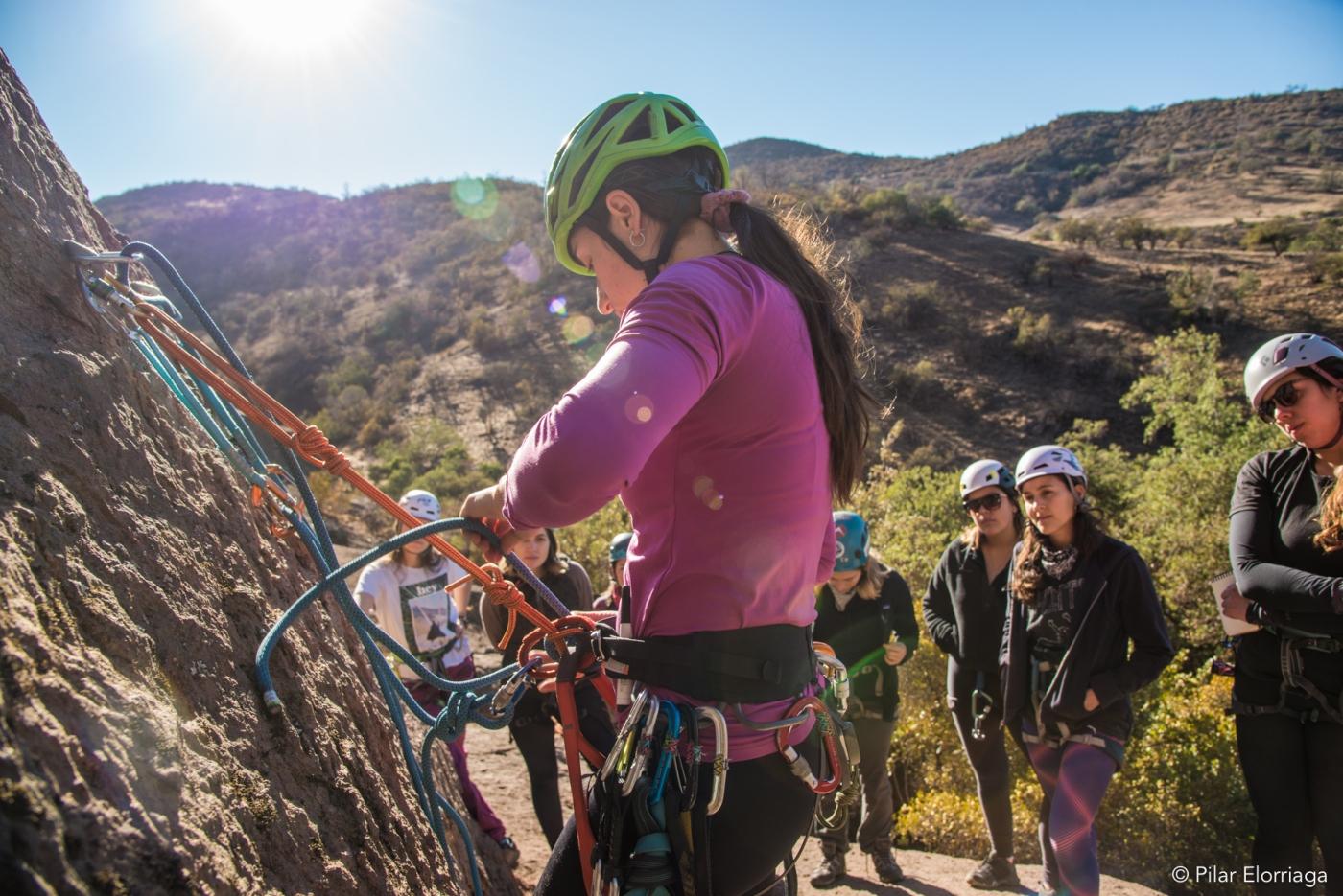 Mujeres en ruta. Deportista preparando su equipo para practicar escalada en Chile