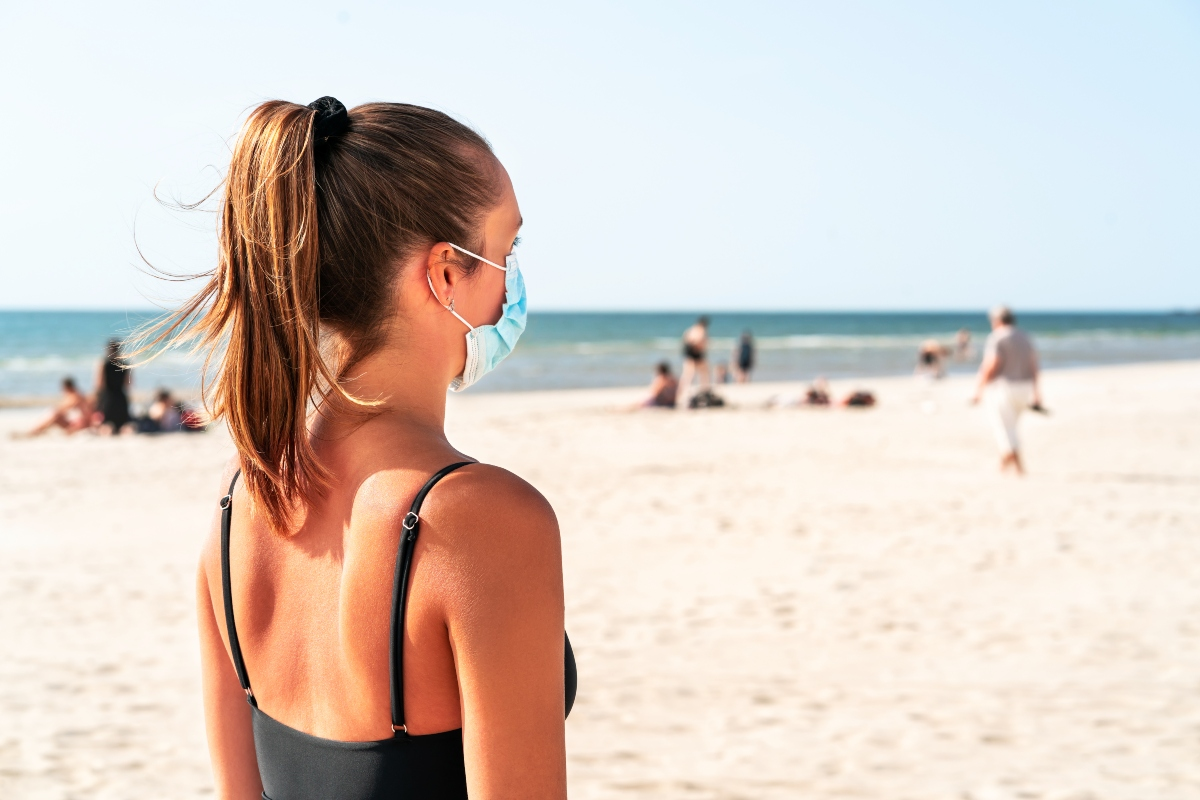 Verano responsable. mujer en la playa con mascarilla