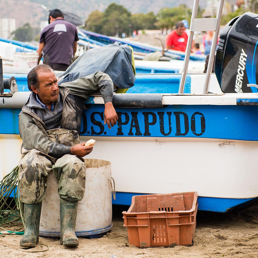 Pescador sentado al lado de su barco