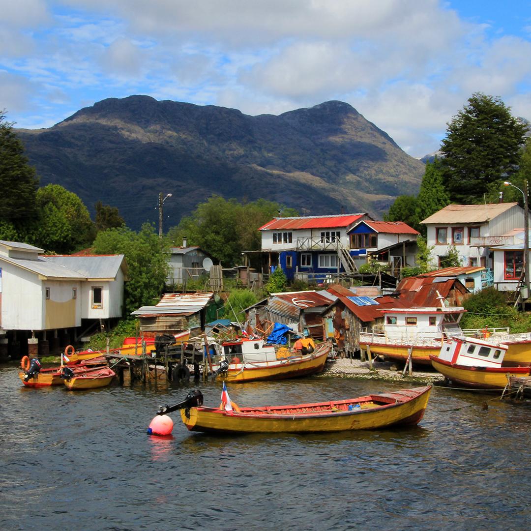 Botes de pescadores en la bahía junto a casas al borde del mar