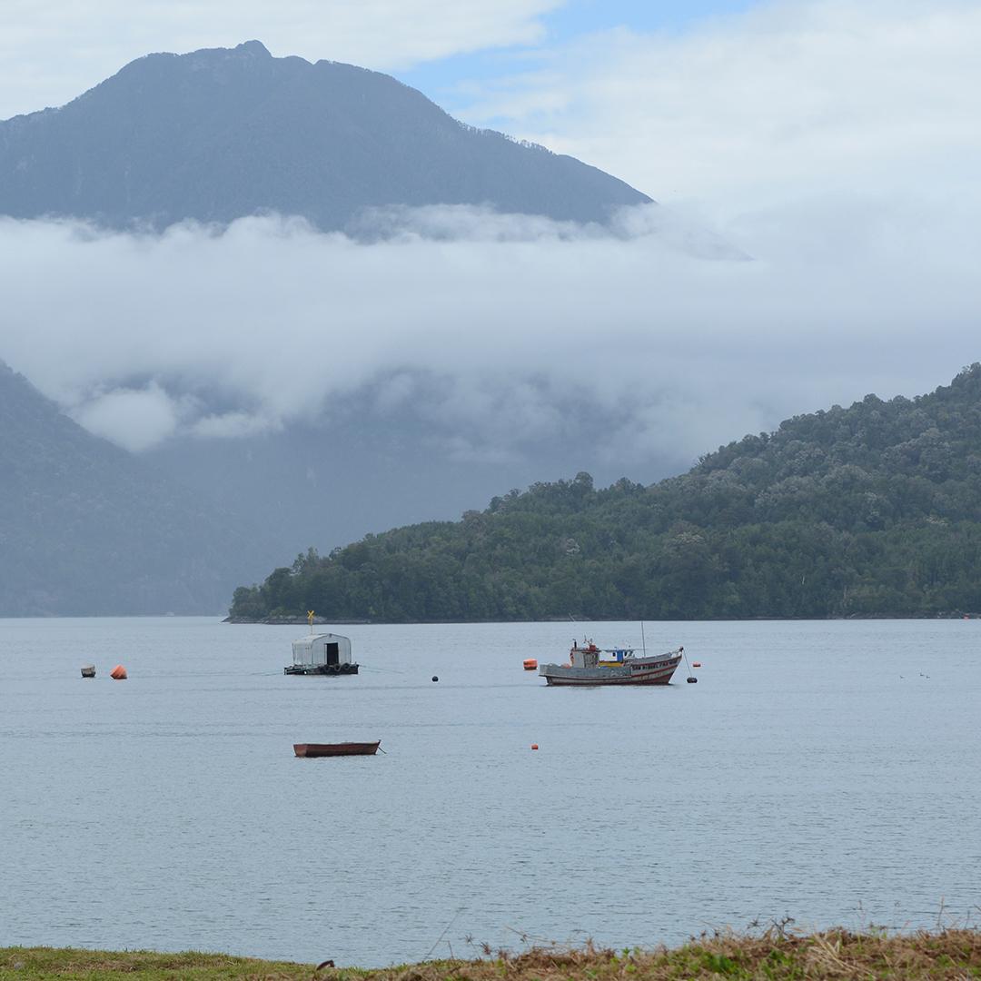 Vista panorámica de barcos pescadores en el mar entre nubes y montañas