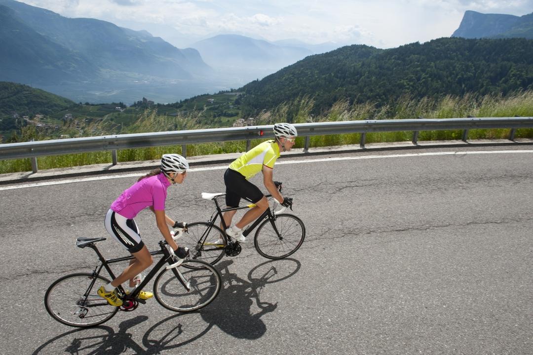 hombre y mujer en bicicleta en subida por carretera
